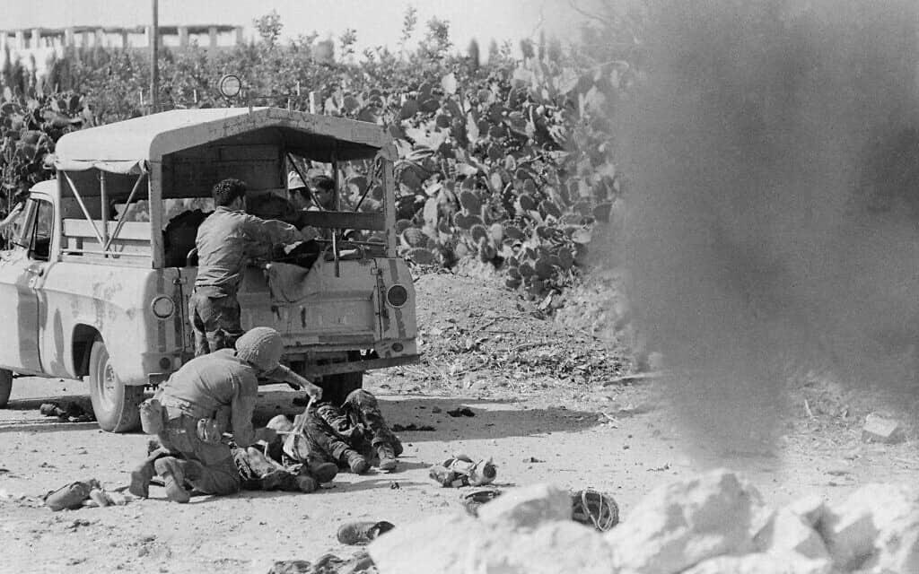 חייל ישראלי מושיט עזרה לפצוע ממטען חבלה שהשאירו המצרים כאשר נסוגו מעזה, יוני 1967 (צילום: AP Photo/Kurt Strumpf)