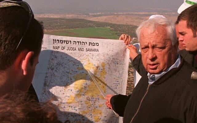אריאל שרון ב-29 בדצמבר 1997, אז שר התשתיות, מסביר למלוויו ולתקשורת בגדה המערבית שהיהודים חייבים לאכלס את הגבעות הצופות על בקעת הירדן (צילום: AP Photo/Eyal Warshavsky)