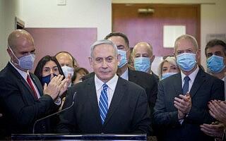 חברי הליכוד עומדים סביב בנימין נתניהו בבית המשפט המחוזי בירושלים, לפני פתיחת משפטו, ב-24 במאי 2020 (צילום: יונתן זינדל/פלאש90)