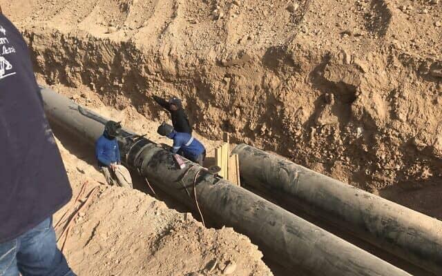 """פועלים פלסטינים עובדים על הנחת צינור הביוב במט""""ש נחל אוג (צילום: אמיר בן-דוד)"""