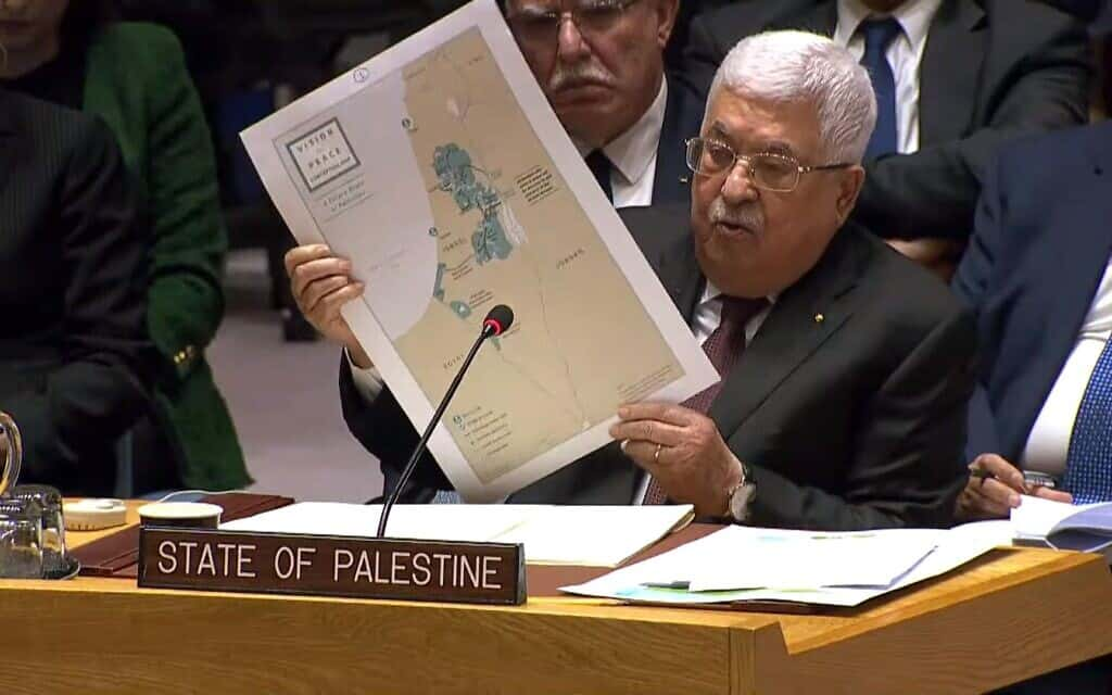 """יושב ראש הרשות הפלסטינית, מחמוד עבאס, מדבר במועצת הביטחון של האו""""ם ב-11 בפברואר 2020, כשהוא מחזיק בידיו מפה מתוך תוכנית השלום הישראלי-פלסטיני של ארצות הברית (צילום: צילום מסך)"""