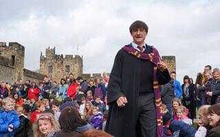 אילוסטרציה, שחקן שמגלם את הארי פוטר מדריך סיור מאורגן בטירה באנגליה ששימשה לצילומי כמה מהסרטים בסדרה (צילום: istockphoto/mikeuk)