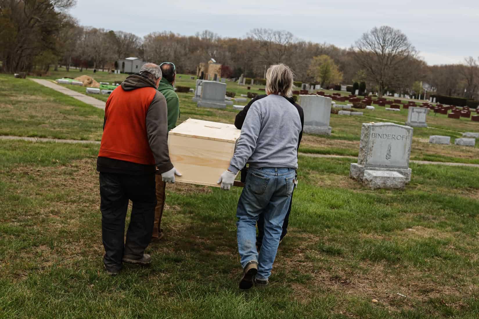 אנשי הצוות בבית הקברות וושינגטון ממוריאל פארק נושאים ארון לקבורה. מאי, 2020 (צילום: Jonathan Alpeyrie/Polaris Images)