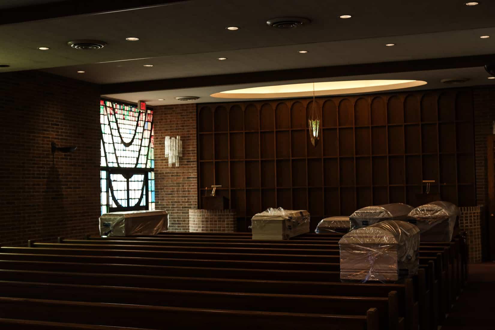 המתים מקורונה ממתינם לקבורה. ארונות הקבורה מונחים בחלל התפילה המרכזי בבית הלוויות גוטרמן, לפני שהם נישאים למקום קבורת העולמים שלהם, בבית הקברות. וודברי, ניו יורק. מאי, 2020 (צילום: Jonathan Alpeyrie/Polaris Images)
