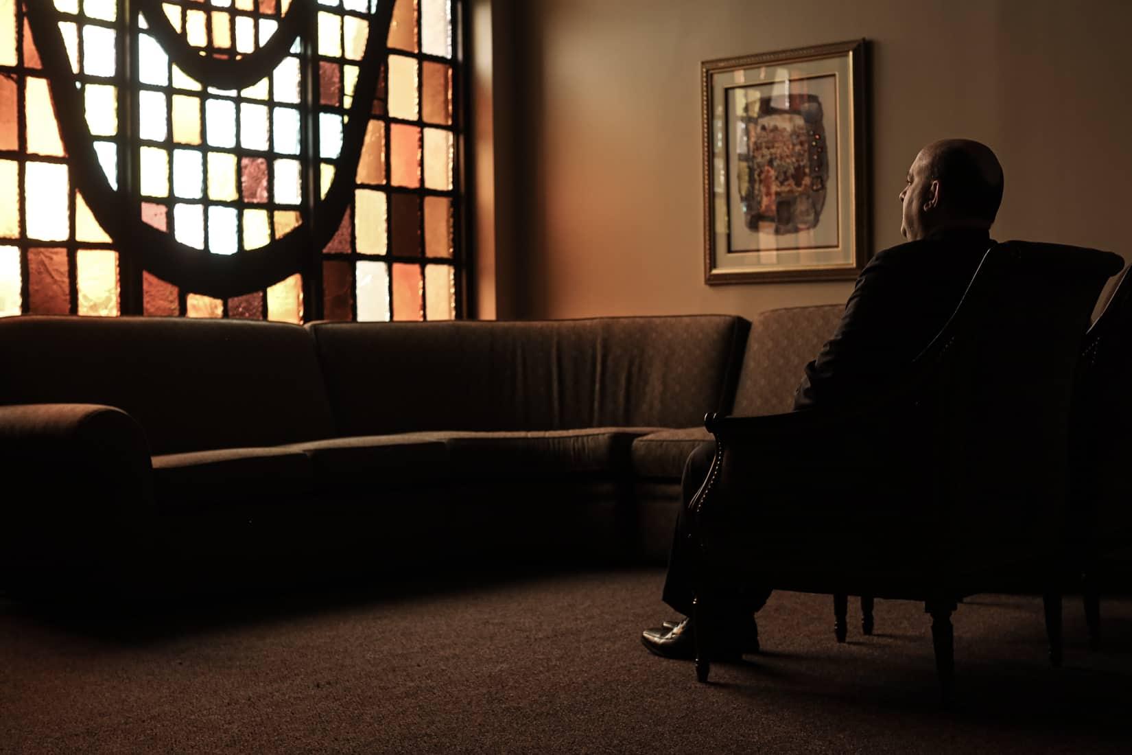 מנהל בית הלוויות גוטרמן, דומיניק קרלה, יושב באחד מחדרי ההמתנה שבו נהגו משפחות להתאבל. וודברי, ניו יורק. מאי, 2020 (צילום: Jonathan Alpeyrie/Polaris Images)