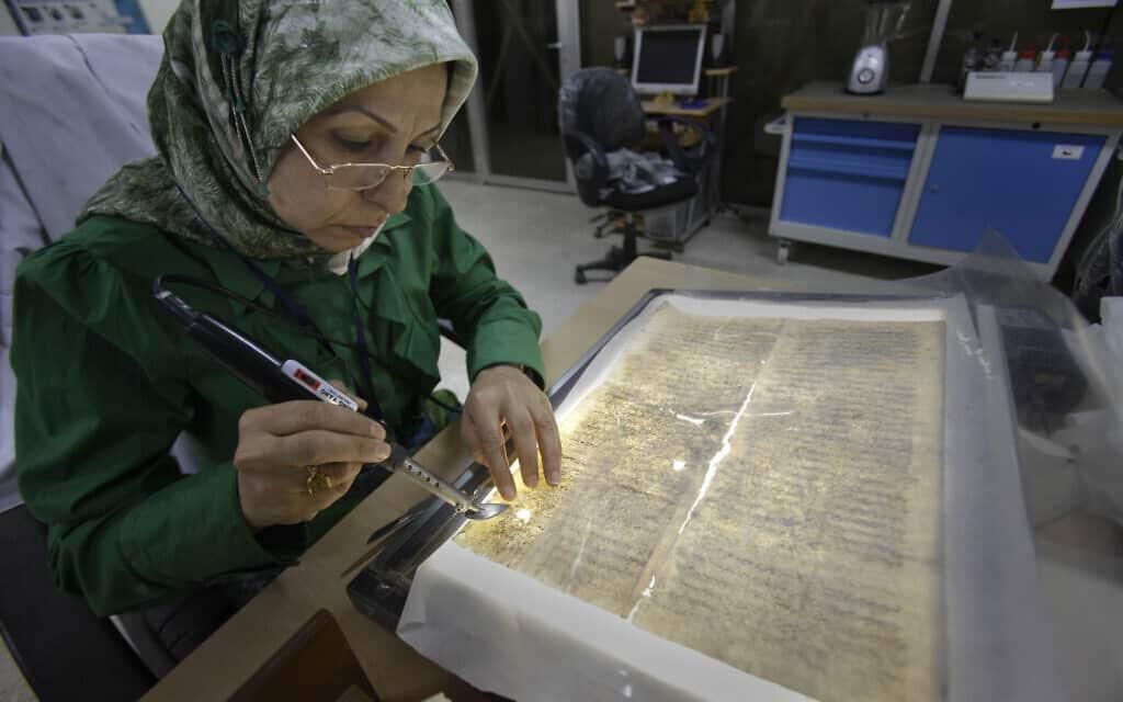 עובדת בספריה העיראקית הלאומית חוקרת ומשמרת כתבים יהודיים עתיקים שהתגלו במדינה, 2011 (צילום: AP Photo/Khalid Mohammed)