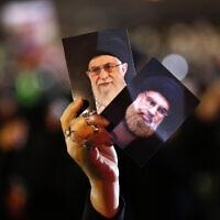 תומך חזבאללה מחזיק תמונות של מנהיג חזבאללה שיח' חסן נצראללה ושל המנהיג העליון של איראן אייטולה ח'מנאי (צילום: AP Photo/Hussein Malla)