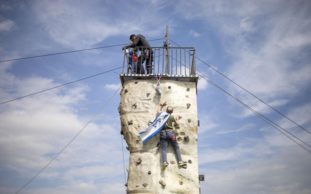 צעיר מנסה להניף את דגל ישראל בבקעת הירדן, פברואר 2020 (צילום: AP Photo/Ariel Schalit)