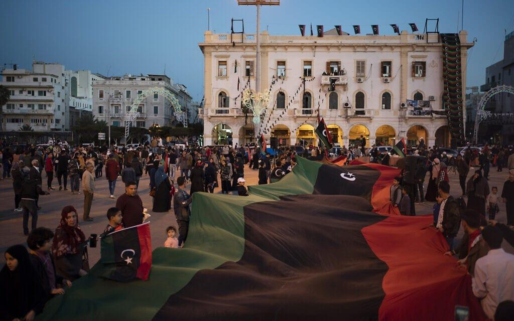 דגל לוב נישא בטקס לזכר הרוגי המחאה נגד קדאפי, טריפולי, פברואר 2020 (צילום: AP Photo/Felipe Dana)