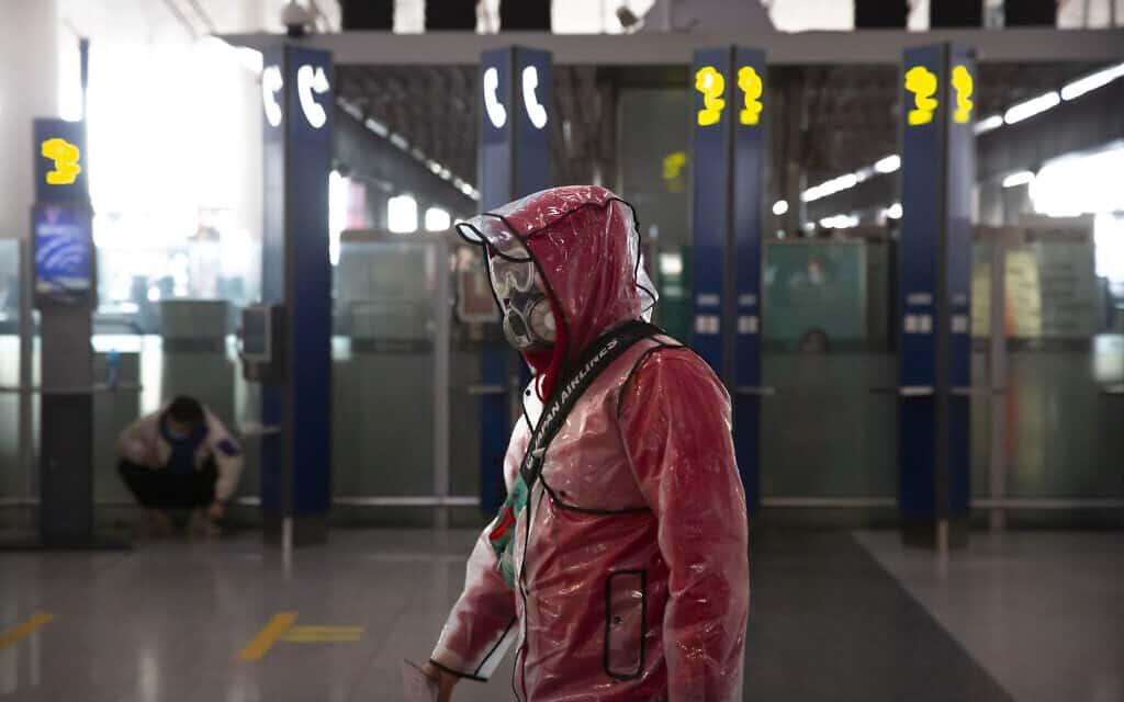 אילוסטרציה, נוסע ממוגן בשדה התעופה של בייגי'נג, 28 במרץ 2020 (צילום: AP Photo/Mark Schiefelbein)