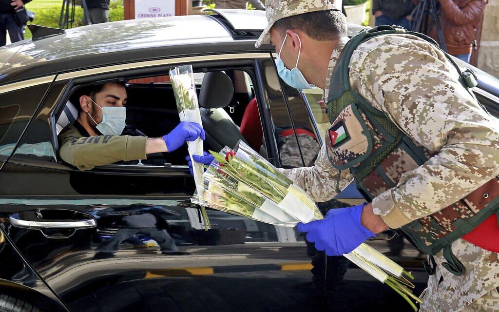 עידן הקורונה בירדן, חיילים מחלקים פרחים לתושבים שהיו נתונים בהסגר ממושך (צילום: Khalil Mazraawi/Pool via AP)