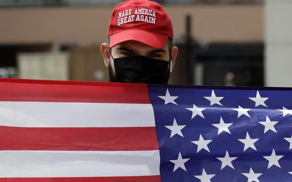 תומך טראמפ מפגין נגד הסיוע למהגרים במשבר הקורונה, לוס אנג'לס, 31 במרץ 2020 (צילום: AP Photo/Marcio Jose Sanchez)