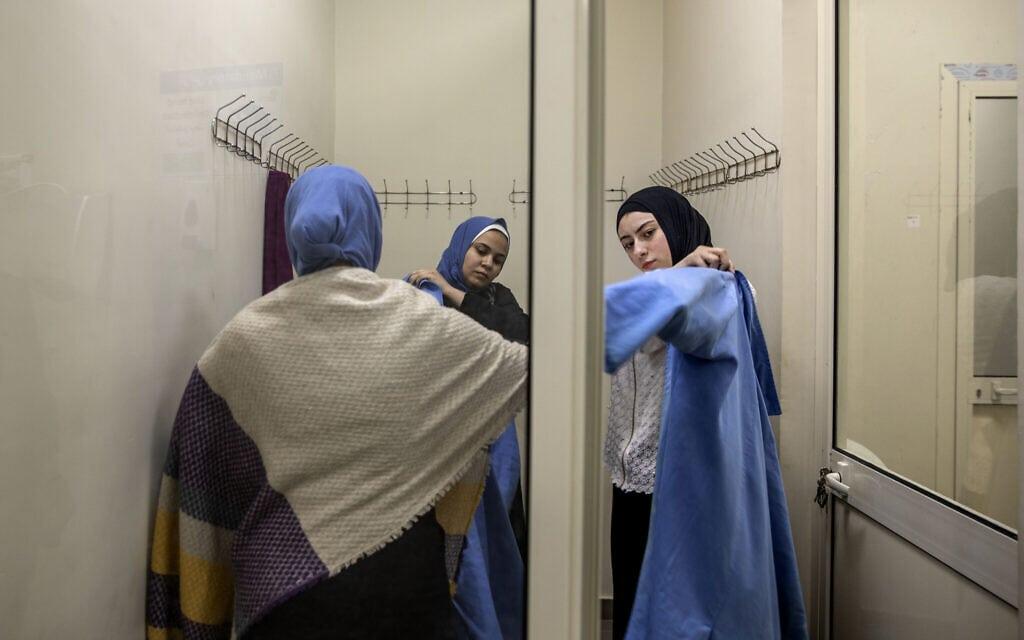 נשים מצריות מתלבשות לעבודתן במפעל לאריזת תפוזים, אפריל 2020 (צילום: AP Photo/Nariman El-Mofty)
