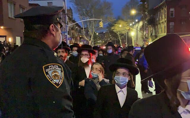 שוטר בעיר ניו יורק משגיח על מאות אבלים במסע הלוויה של הרב החסידי חיים מרץ, שנפטר לאחר שנדבק בנגיף הקורונה, בברוקלין, ניו יורק, 28 באפריל 2020 (צילום: פיטר גרבר באמצעות AP)