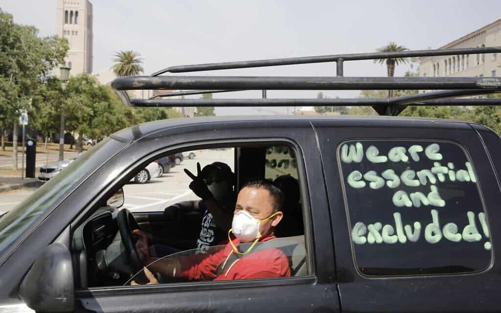 """פועלים ותומכים בפסדינה מקיימים """"הפגנת מכוניות בטוחה"""" כדי להפגין נגד מה שהם תופסים כהדרת פועלים מהגנה כלכלית במסגרת המגפה. מחוץ לעירייה בפסדינה, קליפורניה, אפריל, 2020 (צילום: AP Photo/ Damian Dovarganes)"""