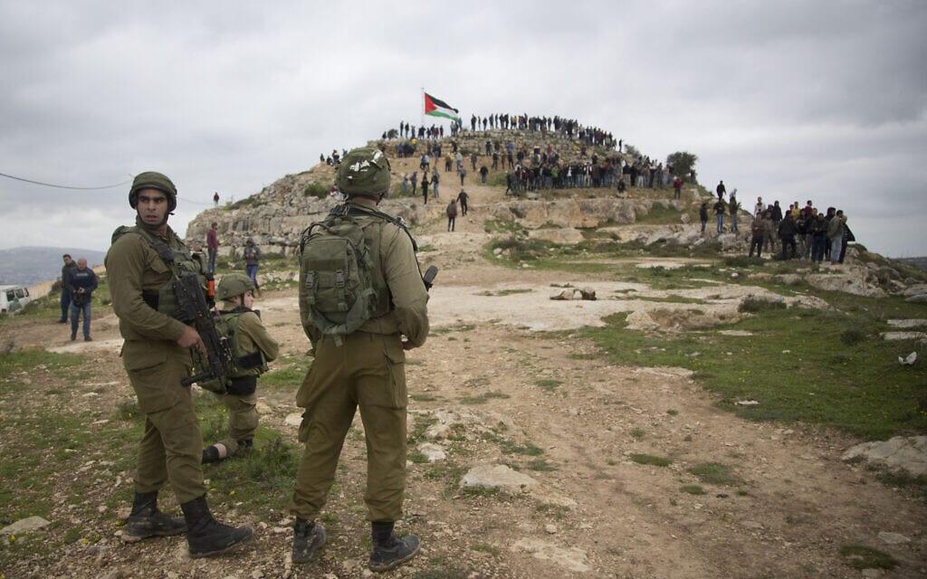חיילים צופים במחאה פלסטינית נגד הסיפוח בגדה המערבית, מרץ 2020 (צילום: AP Photo/Majdi Mohammed, File)
