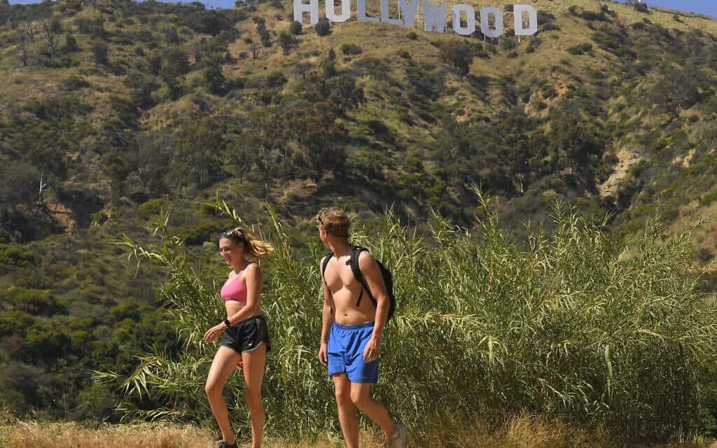 מטיילים ליד שלט הוליווד בקליפורניה, 28 במאי 2020. חלק מהפארקים כבר נפתחו מחדש (צילום: AP Photo/Mark J. Terrill)