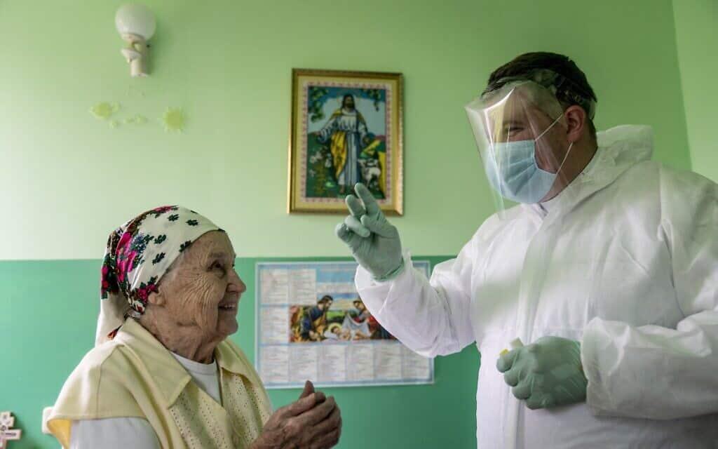 אילוסטרציה, חולת קורונה מבוגרת באוקראינה (צילום: AP Photo/Evgeniy Maloletka)