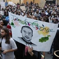 מפגין נושא שלט עם דיוקנו של ג'ורג' פלויד בצעדה לזכרו בסקרמנטו שבקליפורניה, 1 ביוני 2020 (צילום: Rich Pedroncelli, AP)