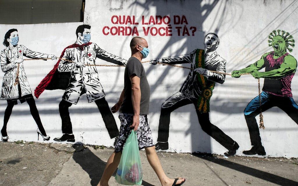 ציור קיר בברזיל המציג את הנשיא כמי שמסייע להתפשטות הקורונה, יוני 2020 (צילום: AP Photo/Leo Correa)