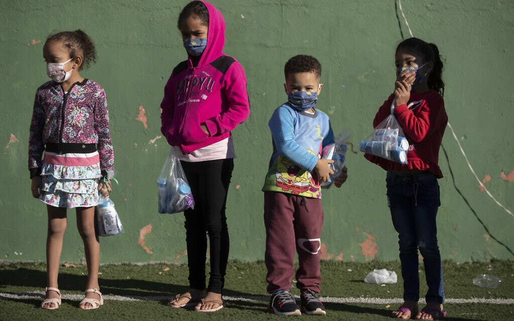 ילדים ברזילאים שקיבלו ציוד אישי למאבק במגפה, יוני 2020 (צילום: AP Photo/Andre Penner)