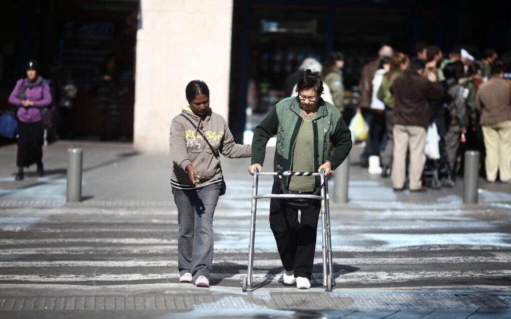 מטפלת פיליפינית מסייעת לקשישה לחצות את הכביש ליד התחנה המרכזית בירושלים. למצולמים אין קשר לנאמר בכתבה (צילום: קובי גדעון/פלאש90)