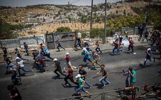 פלסטינים נמלטים מגז מדמיע שפיזרה המשטרה בוואדי ג'וז, ארכיון, 2018 (צילום: Miriam Alster/Flash90)