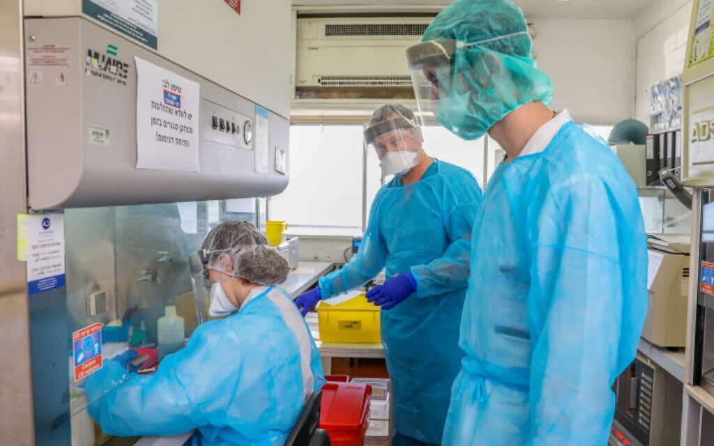 """טכנאים בוחנים בדיקות קורונה במעבדה בבית החולים רמב""""ם בחיפה, 30 במרץ 2020 (צילום: יוסי אלוני, פלאש 90)"""