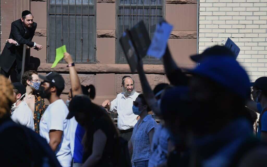 חברי הקהילה האורתודוקסית היהודית מתבוננים במפגינים הצועדים בשכונה בברוקלין ב–3 ביוני 2020 (צילום: Angela Weiss/AFP via Getty Images)