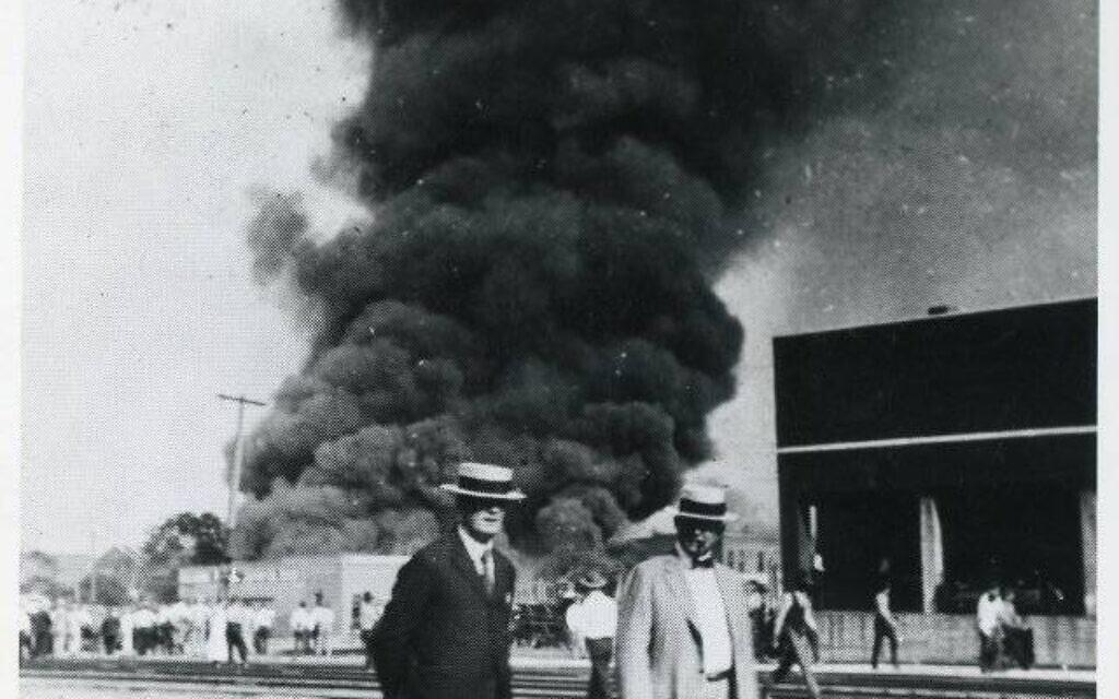 גברים לבנים מצטלמים כשרובע גרינווד בוער מאחוריהם, אחד ביוני, 1921 (צילום: רשות הציבור)
