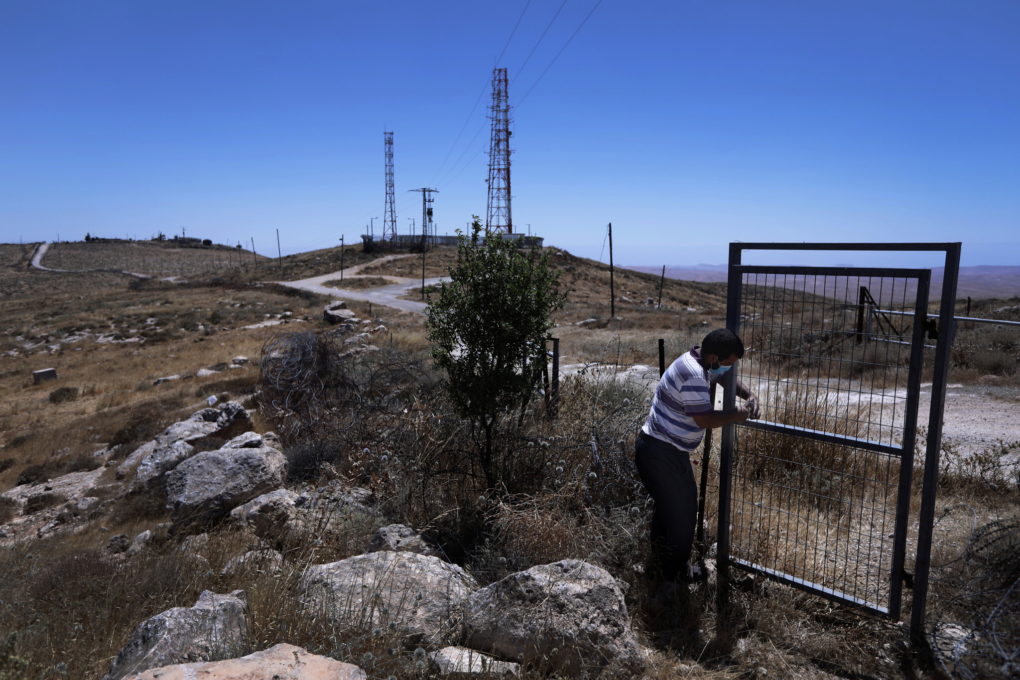 """עתמאן אבו קביטה ליד השער שהציב צה""""ל באמצע השטח שלו (צילום: אלדד רפאלי)"""
