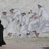 אילוסטרציה, אישה חולפת ליד ציור קיר בדובאי, ארכיון, 2018 (צילום: AP Photo/Jon Gambrell)