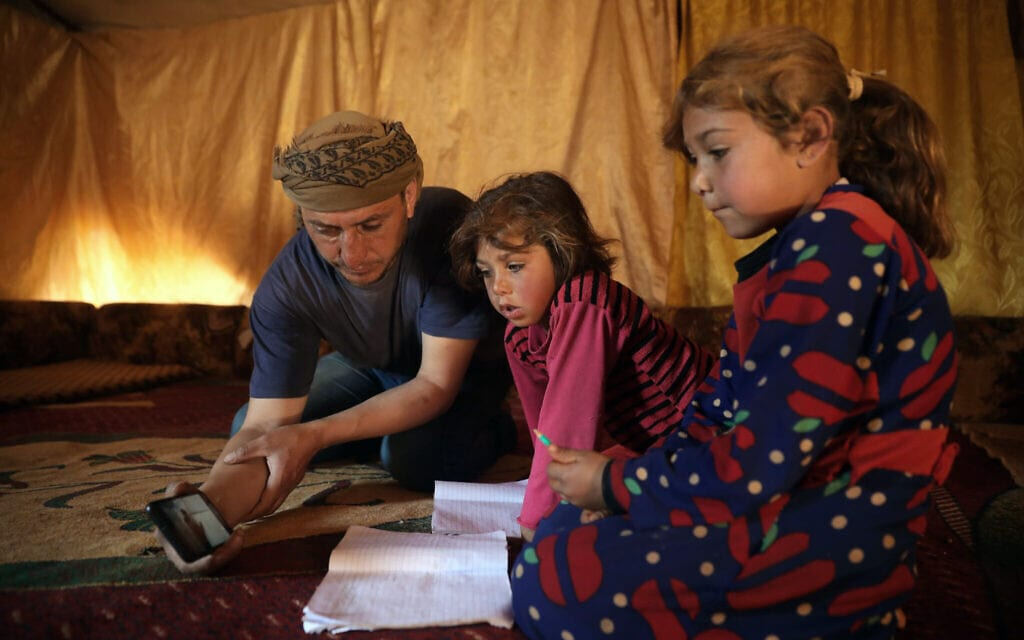אילוסטרציה, ילדות סוריות לומדות מרחוק בעידן הקורונה – באמצעות מכשיר טלפון נייד שאוחז אביהן, אפריל 2020 (צילום: AP Photo/Ghaith Alsayed)