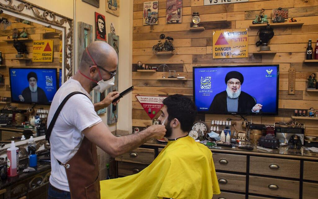 מספרה לבנונית. בטלויזיה מנהיג חזבאללה חסן נסראללה ברשת אל-מנאר, שלט בעברית שנאסף בשטח מזהיר מפני מוקשים (צילום: AP Photo/Hassan Ammar)