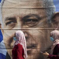 ירושלים, יולי 2020: נשים במסכות חולפות ליד פוסטר של בנימין נתניהו (צילום: AP Photo/Ariel Schalit)
