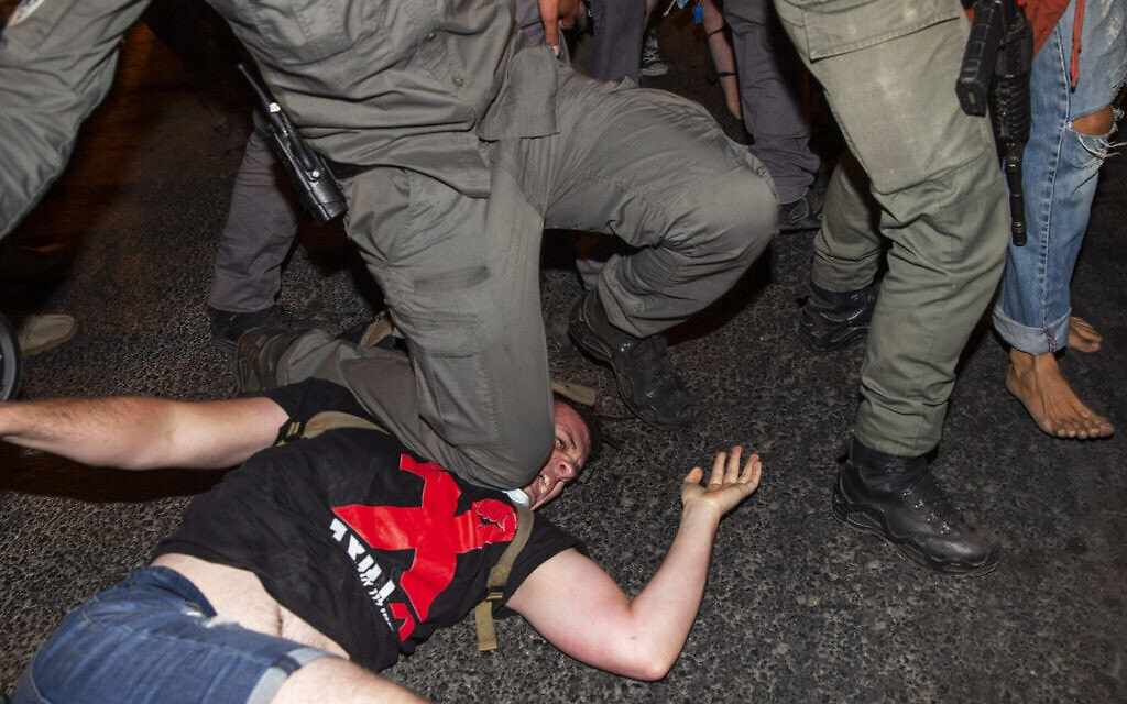שוטר מרתק מפגין תחת ברכו בהפגנה מול בלפור כדי לעצור אותו, 21.7.2020 (צילום: AP Photo/Ariel Schalit)