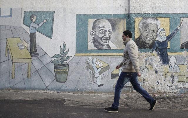 פלסטיני על רקע ציור קיר של נלסון מנדלה ומהטמה גנדי, 2013 (צילום: AP Photo/Adel Hana)