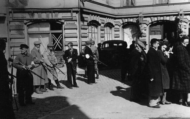 משטרת העזר הלטבית מסייעת בכינוס יהודים בלטביה ב-1941 (צילום: הארכיון הפדרלי הגרמני)