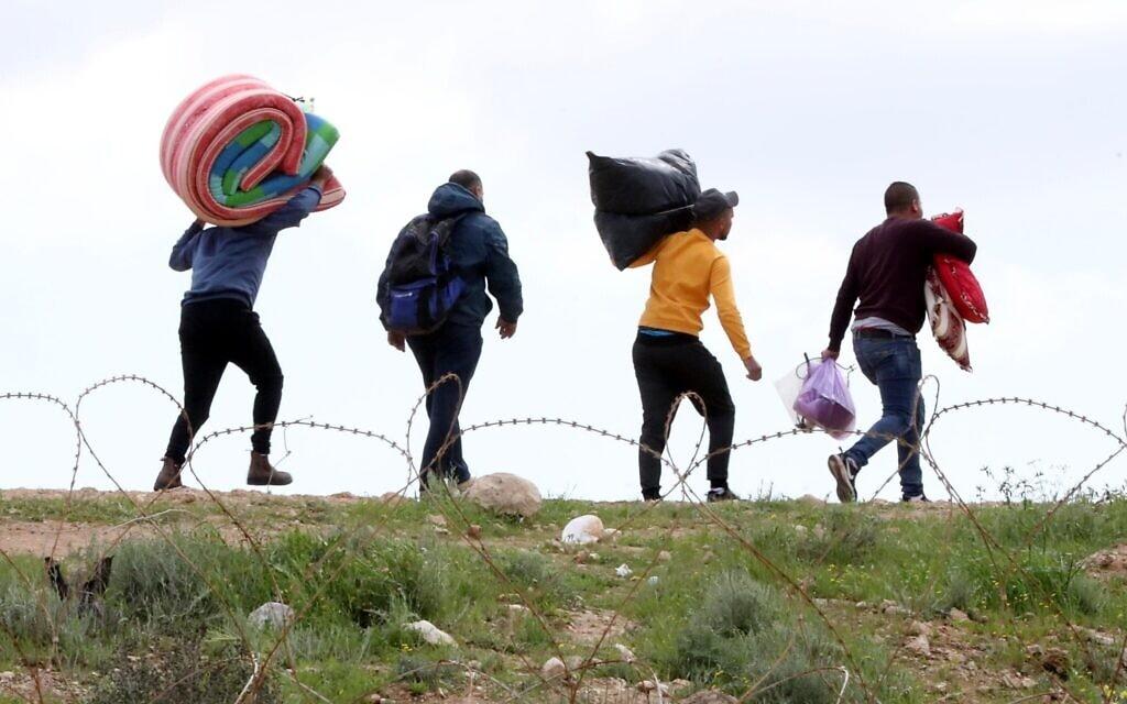 פועלים פלסטינים נכנסים לישראל דרך חור בגדר, לאחר שכניסתם נאסרה בגלל הקורונה, 22 במרץ 2020 (צילום: Wisam Hashlamoun/Flash90)