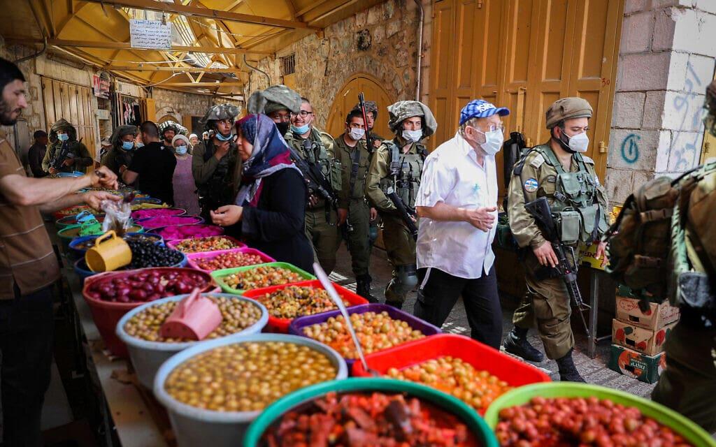 חיילים רבים מלווים סיור של מבקרים יהודים בחברון, 16 במאי 2020 (צילום: Wisam Hashlamoun/Flash90)