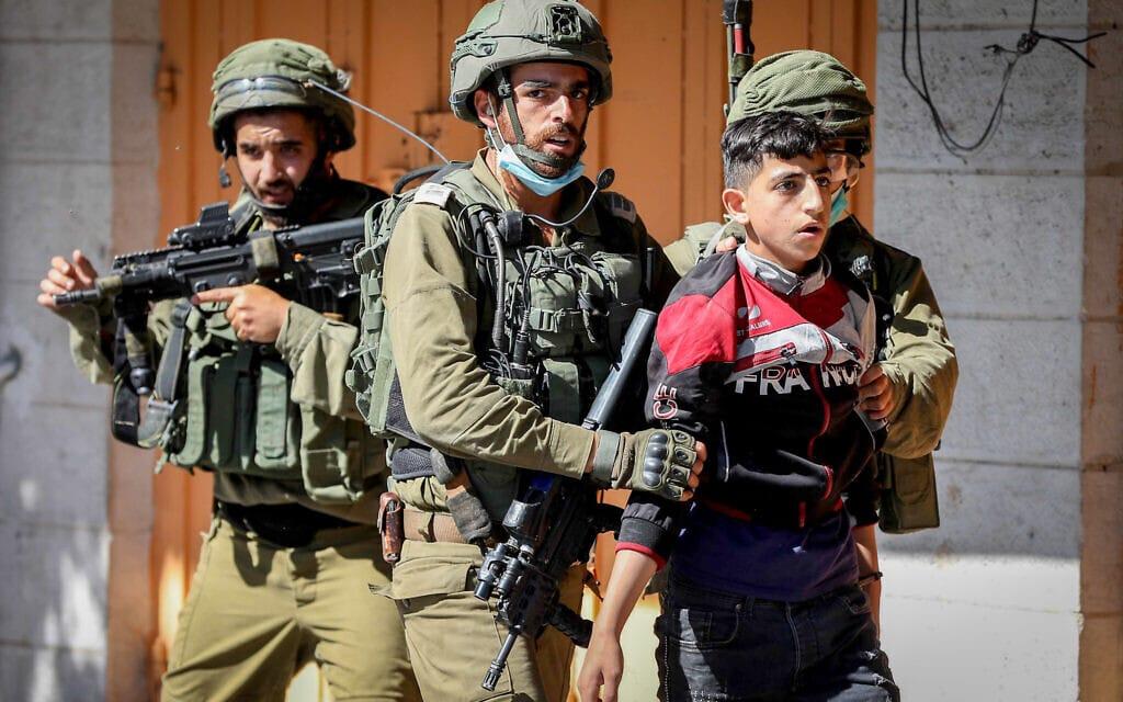 .חיילים עוצרים נער פלסטיני שהפגין נגד תכנית הסיפוח, חברון, 4 ביולי 2020 (צילום: Wisam Hashlamoun/Flash90)