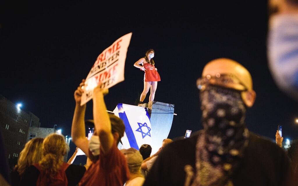 הסטודנטית לעבודה סוציאלית מסירה את חולצתה על פסל המנורה ליד הכנסת. הפגנת בלפור 21.7.2020 (צילום: יאיר מיוחס)