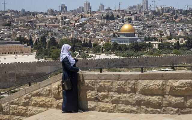 אישה מוסלמית במסכה ובכפפות בהר הזיתים, מתבוננת על כיפת הסלע ואל אקצא – מתחם שנותר סגור כדי למנוע את התפשטות הקורונה, גם בחודש הקדוש של הרמדאן. מאי, 2020 (צילום: אריאל שליט/ AP)