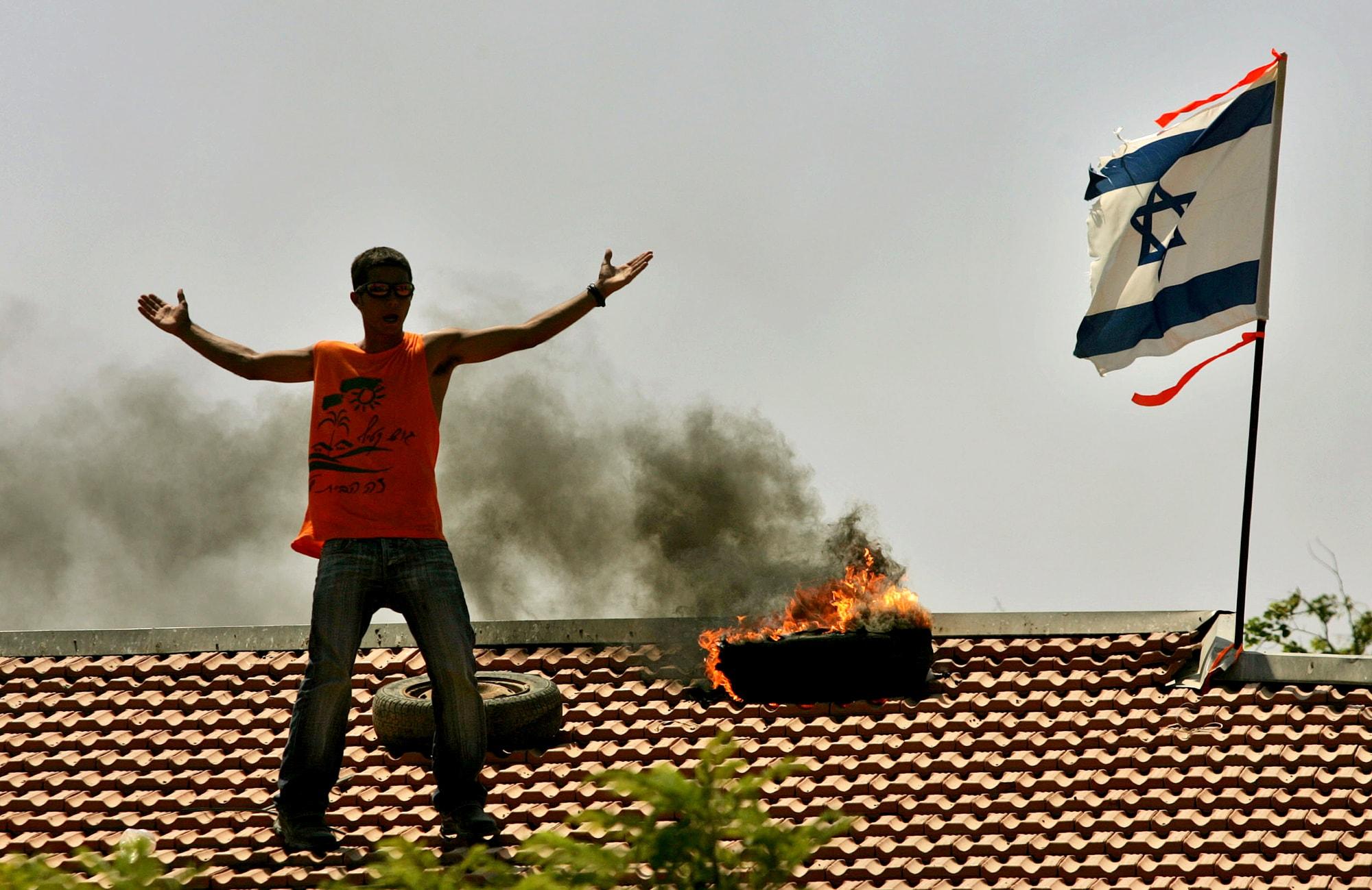 תושב נצר חזני בגוש קטיף על גג ביתו, מקדם את כוחות הביטחון שבאו לבצע את הפינוי במסגרת ההתנתקות, ב-18 באוגוסט 2005 (צילום: AP Photo/Emilio Morenatti)