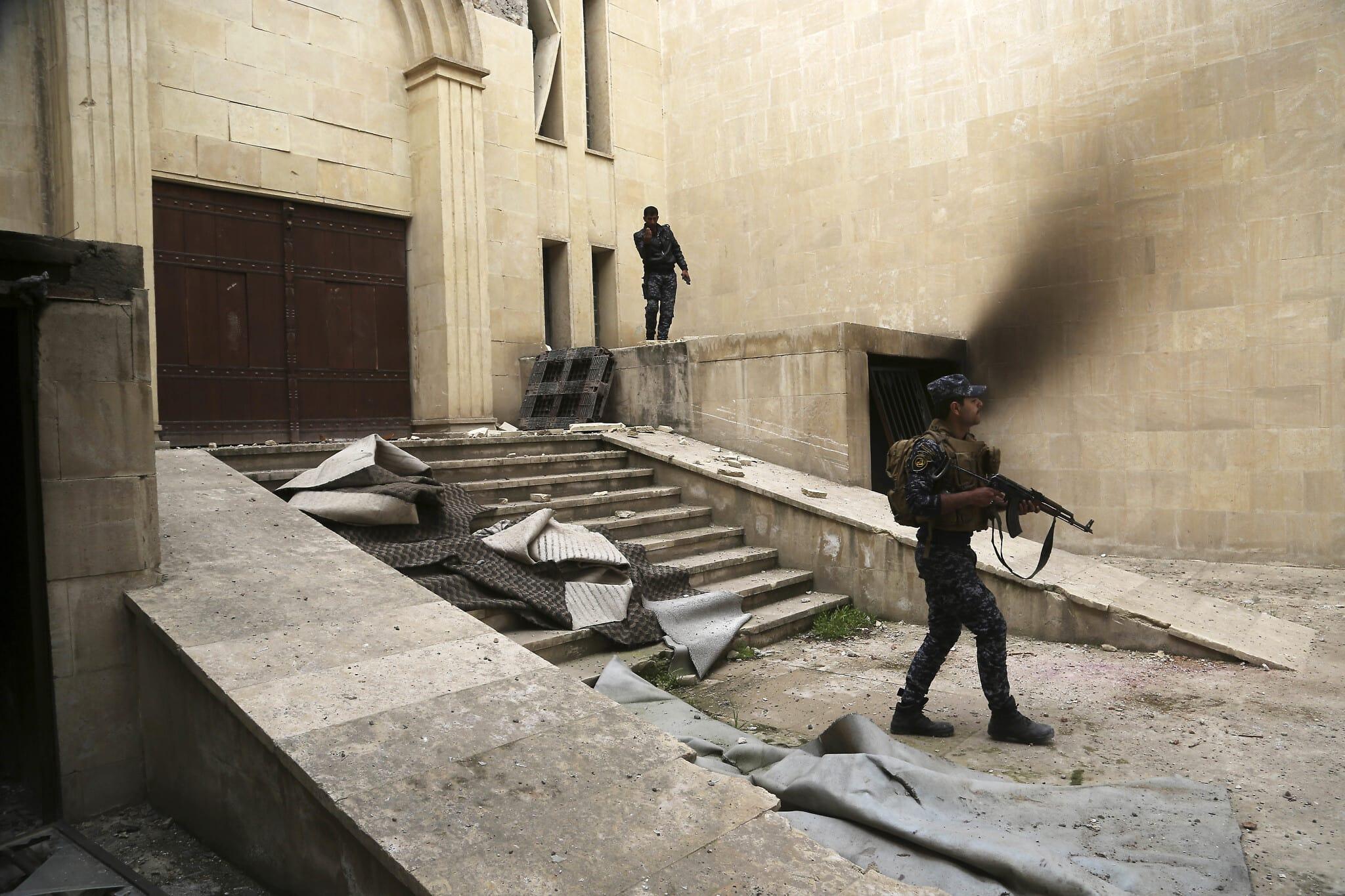 """שוטרים עיראקים בוחנים את ההרס שהותירו אנשי דאע""""ש במוזיאון של מוסול, ב-8 במרץ 2017 (צילום: AP Photo/Khalid Mohammed)"""