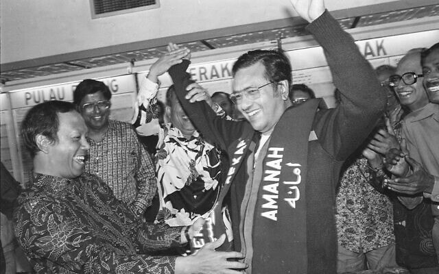 בתמונה הזאת, שצולמה ב-23 באפריל, 1982, ראש הממשלה המלזי מאהאטיר מוחמד מרים את ידיו בניצחון כשסגנו, מוסא חיטאם, מניח עליו סרט בקואלה למפור, מלזיה (צילום: AP)