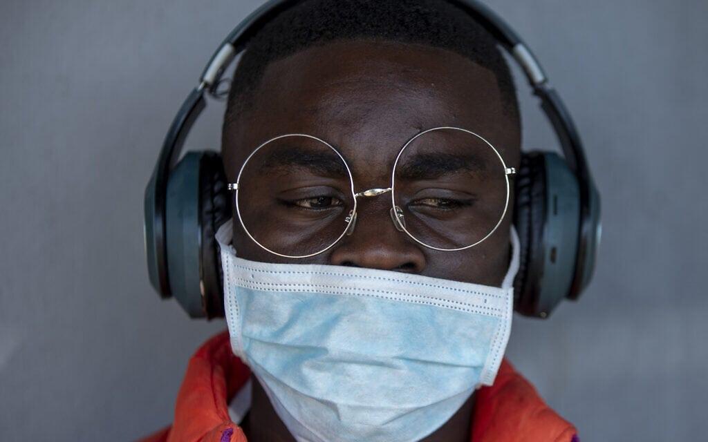 ספר לובש מסכה להגנה מפני וירוס הקורונה, דרום אפריקה, מרץ 2020 (צילום: AP Photo/Themba Hadebe)