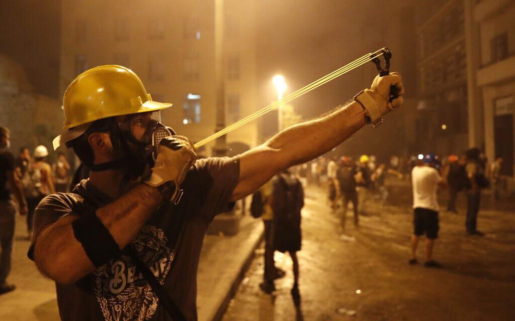 מפגינים בלבנון נלחמים באמצעי פיזור ההפגנות של המשטרה, 2020 (צילום: AP Photo/Hussein Malla)