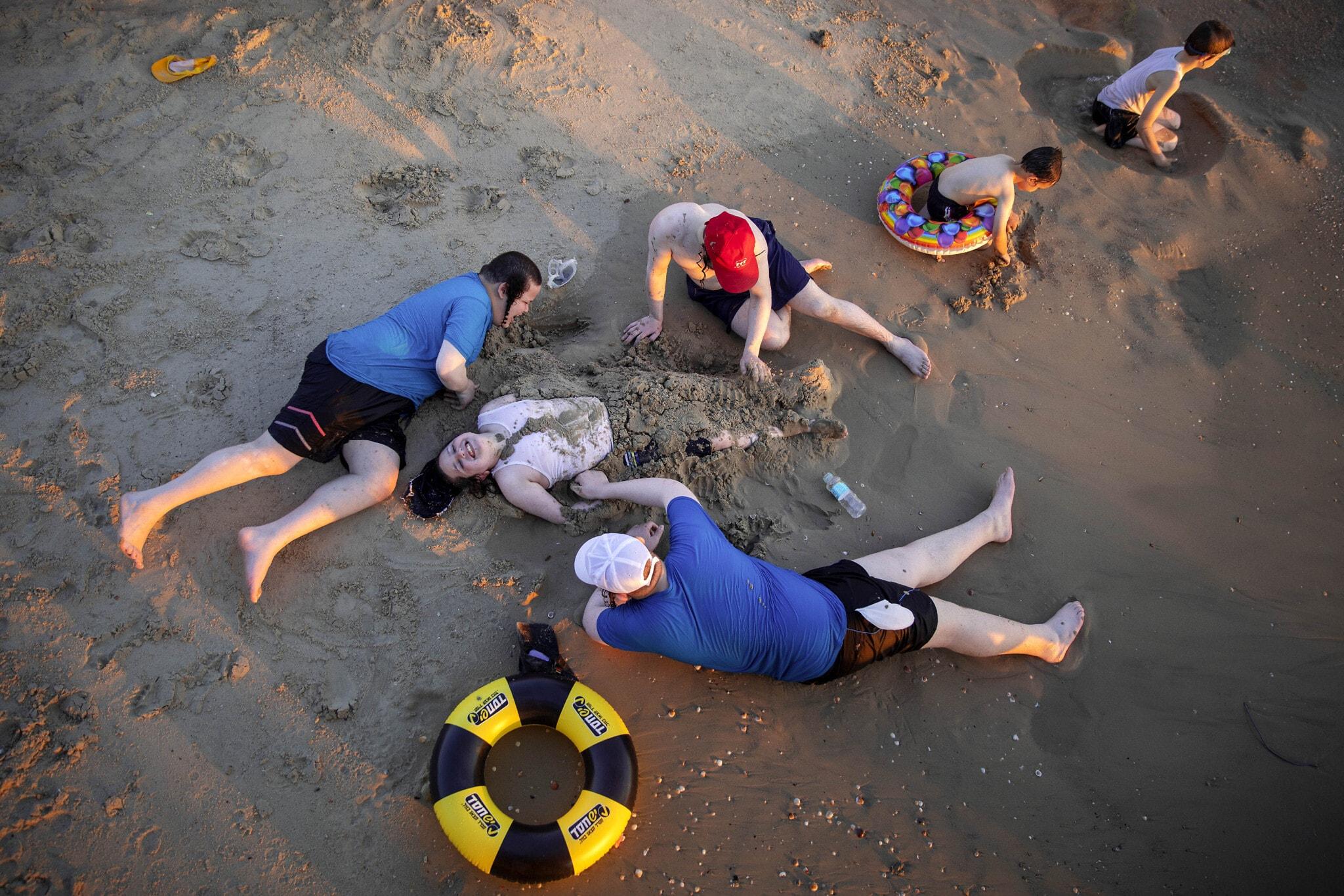 אילוסטרציה, משפחה חרדית (גברים בלבד) רוחצת בחוף הים של תל אביב כהפוגה משגרת הקורונה, אוגוסט 2020 (צילום: AP Photo/Oded Balilty)