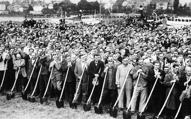 פועלים אוחזים אתים ומקשיבים לנאומו של אדולף היטלר עם תחילת העבודות על הכביש המהיר מפרנקפורט על המיין להיידלברג, 23 בספטמבר 1933 (צילום: AP)
